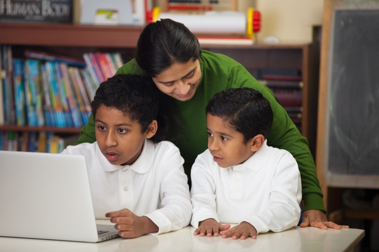 A latino family sits in front of a computer doing schoolwork.